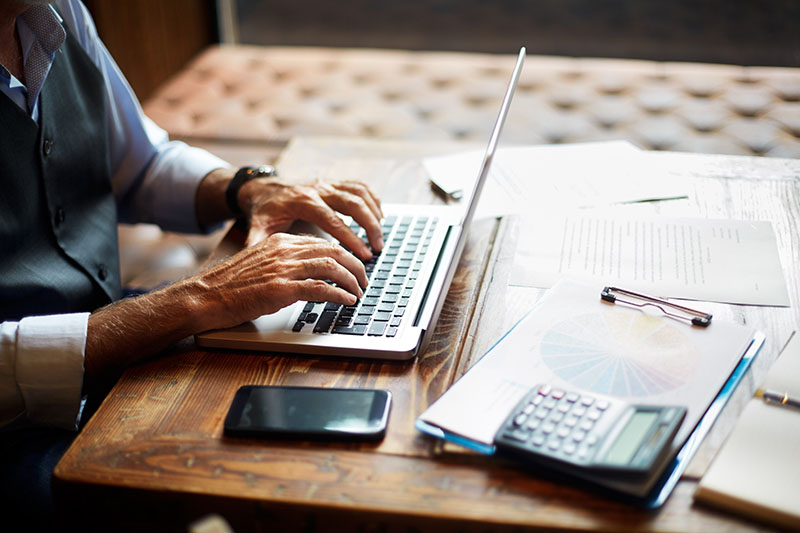 A man types on his laptop at a table covered in work papers