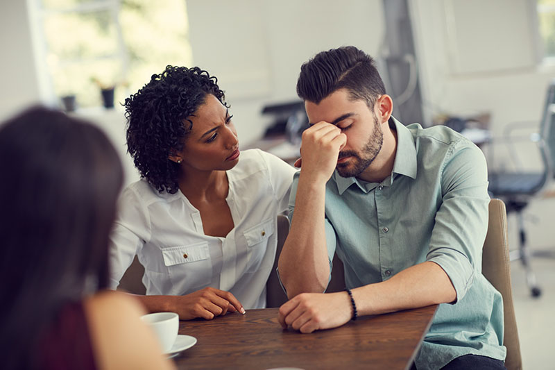 One person comforts another in a support group