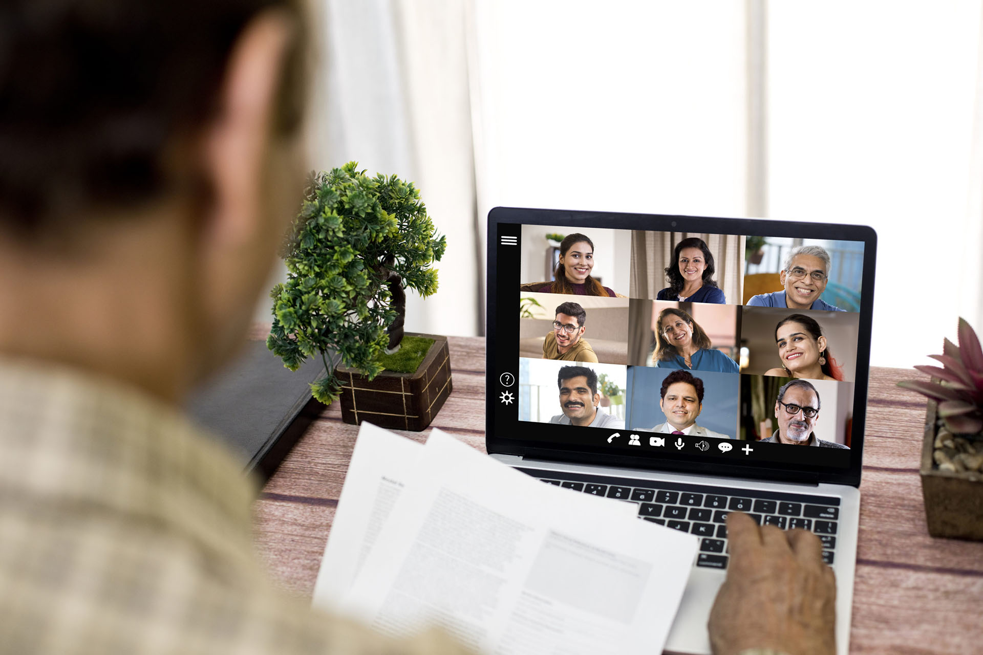 A man attends a remote video conference meeting on laptop at home