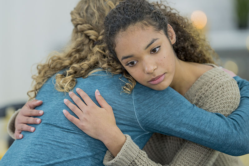 A young woman embraces another person while she stares blankly